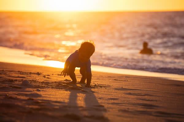 happy little boy playing on beach sunset light
